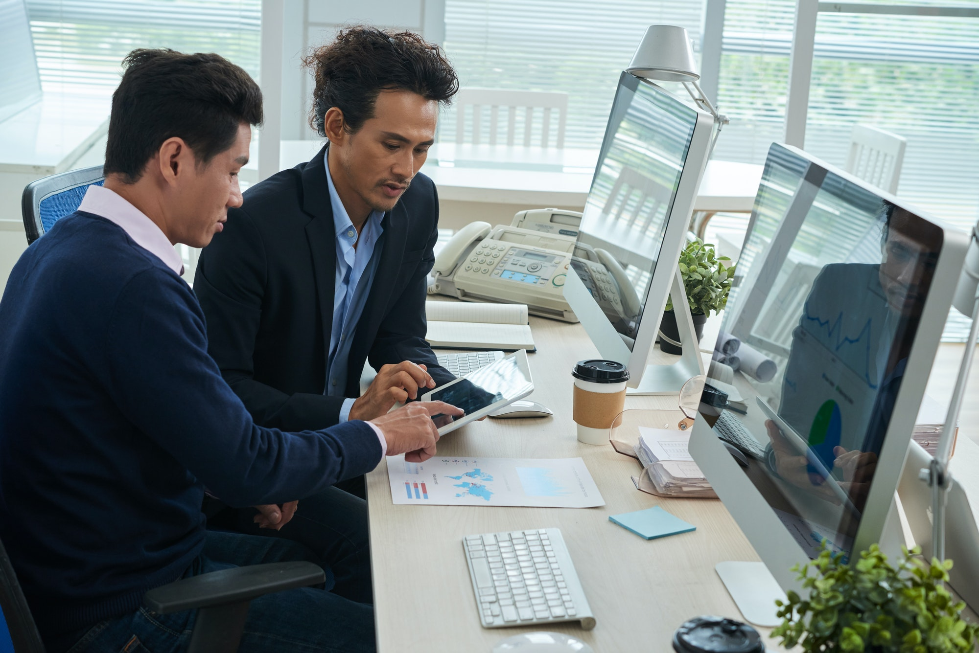 Businessmen working with finance data on tablet